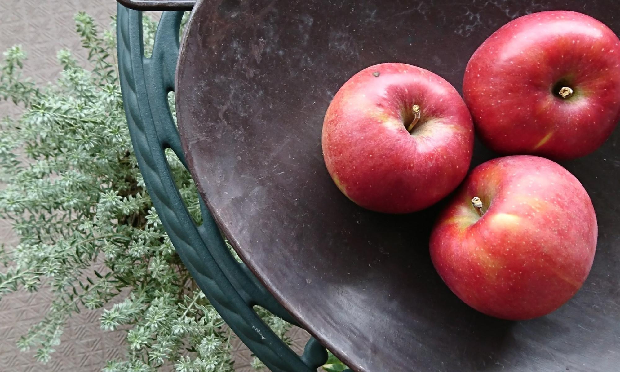 黒皿に真っ赤な林檎が3つ並んでます。