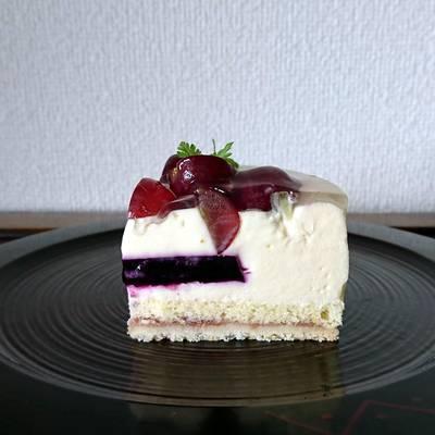 黒くて丸く平らなお皿に乗せた赤葡萄と白ワインのムースケーキ