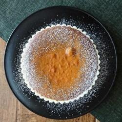 黒の丸皿に乗ったパンプキンパイ。