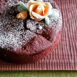 バラ(菓子)がデコレーションされたガトーショコラが木の器にのっています。
