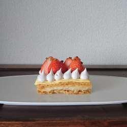 白のお皿に苺とクリームがのったパイ菓子