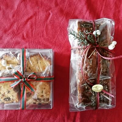 真っ赤なクロスの上にクリスマス仕様のラッピングされたフルーツケーキが並んでいます。