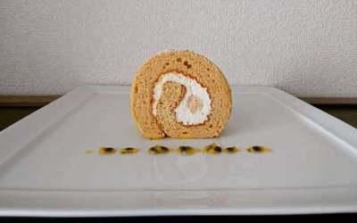 白いお皿にカットされたロールケーキとソースが並んでいます。
