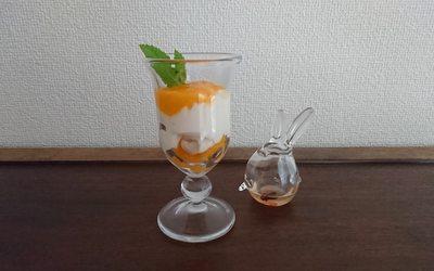 白いプリンとマンゴーソース・ミントがグラスに盛り付けられています。