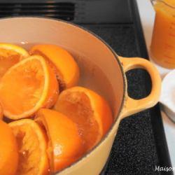 半割のオレンジが大鍋に水と共に入り火にかけています