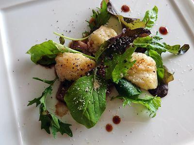 白いお皿の上に緑の野菜とお肉と桃が盛り付けられています。