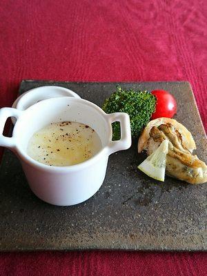 白い小さな器に入ったスープとソテーした牡蠣がお皿の上で並んでいます
