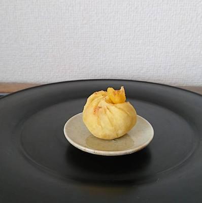 漆黒盆の上に豆皿にのった栗の茶巾しぼりが1つ