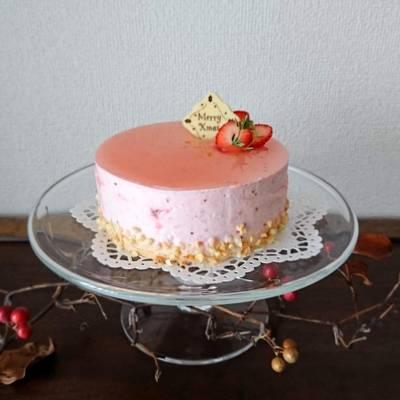 ガラスのケーキスタンドにストロベリームースのホールケーキがあります
