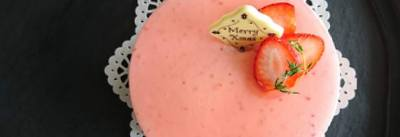 漆黒盆の上にピンクの苺ムースケーキのホールがあります
