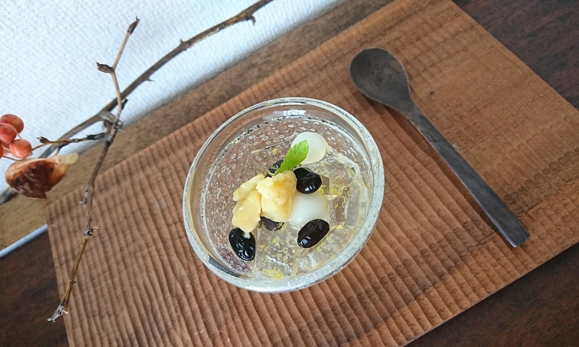 柚子ゼリーと黒豆・白玉団子・栗きんとんが盛り付けられたガラスの器が木盆に
