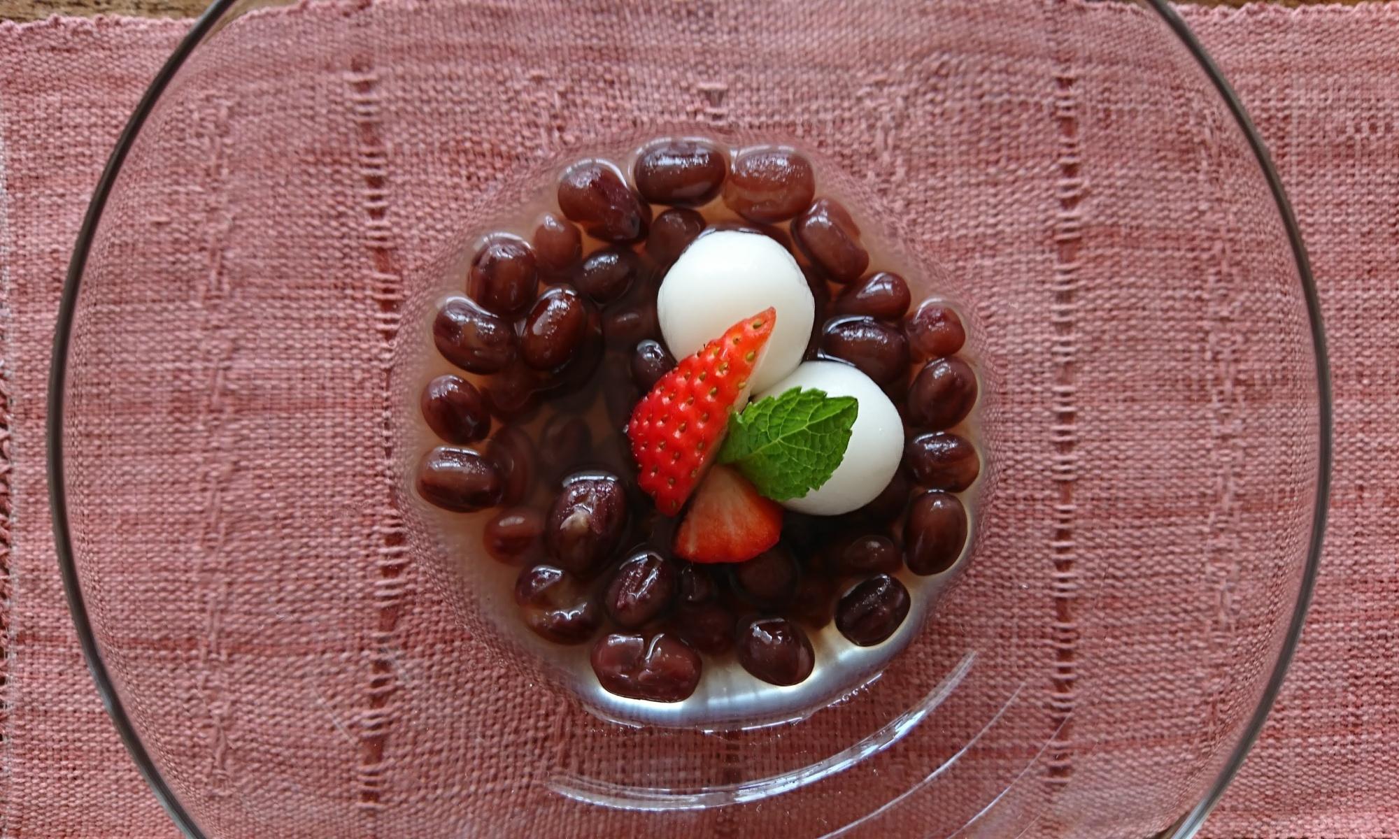 ガラスの器にぜんざいと丸い白玉団子、苺とミントが盛り付けられています
