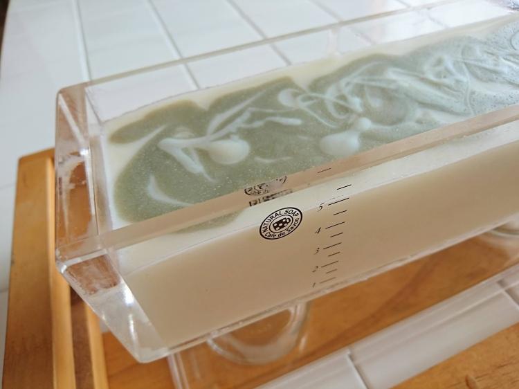 透明な四角い石鹸型に石鹸液を流し込まれた状態