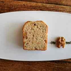 白皿の上にカットされたパウンドケーキと胡桃と茶葉が盛り付けられている