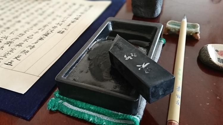 硯の上に墨が乗り横には筆と写経した半紙が並んでいます。