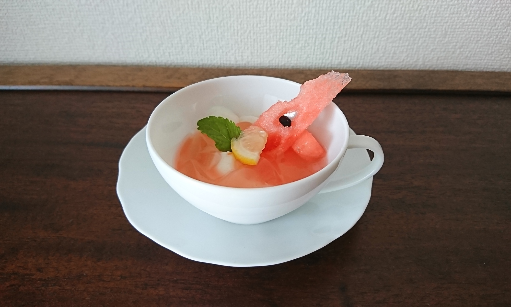 白いカップ&ソーサーにスイカのジュレがかかった杏仁豆腐が盛り付けられています。