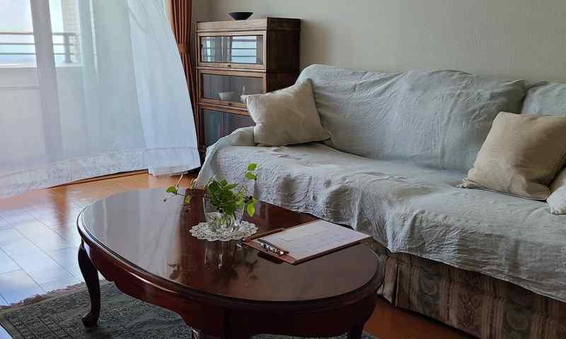 風で揺れるカーテン、ソファー&テーブルが置かれたリビング