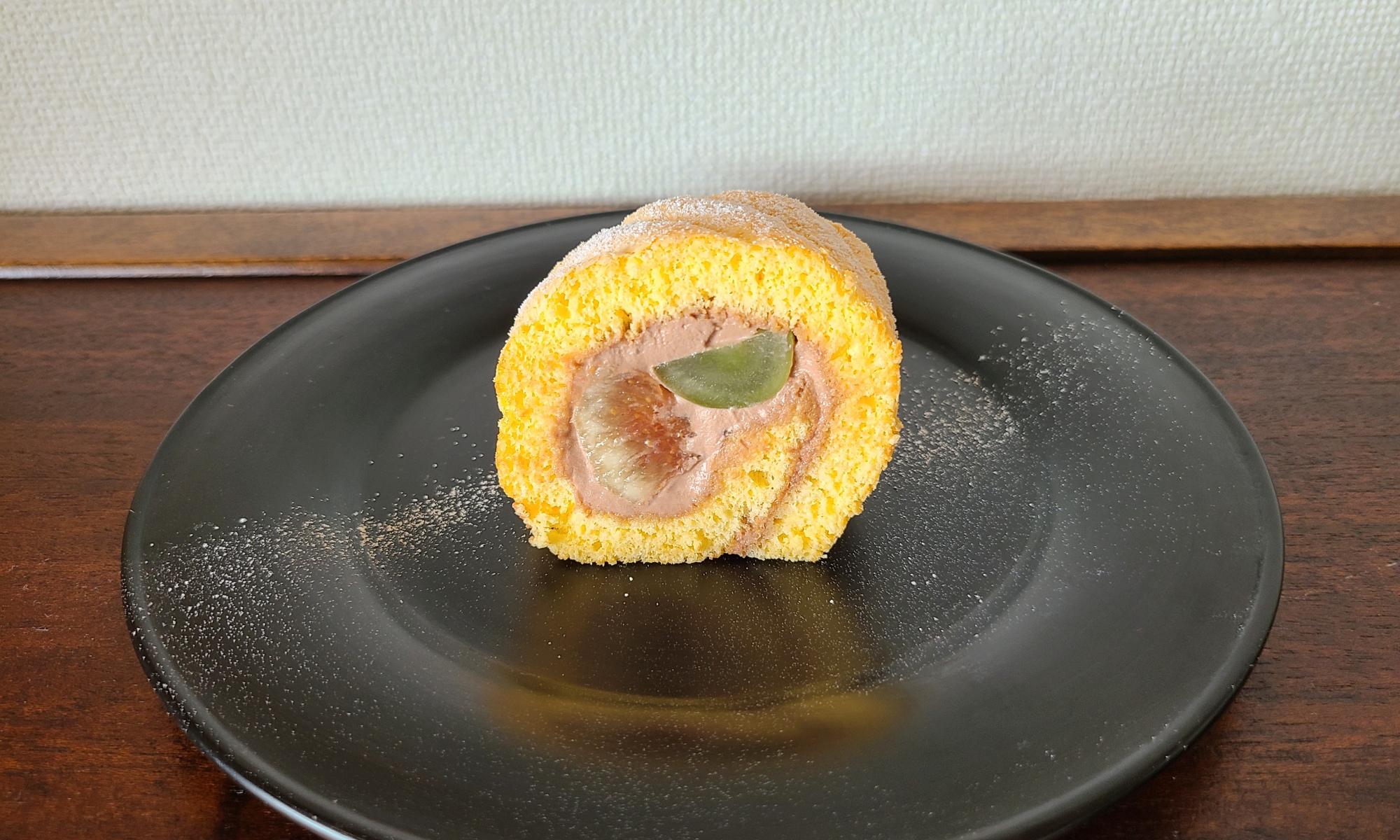 漆黒の器に秋の果実を巻いたロールケーキが1カット。