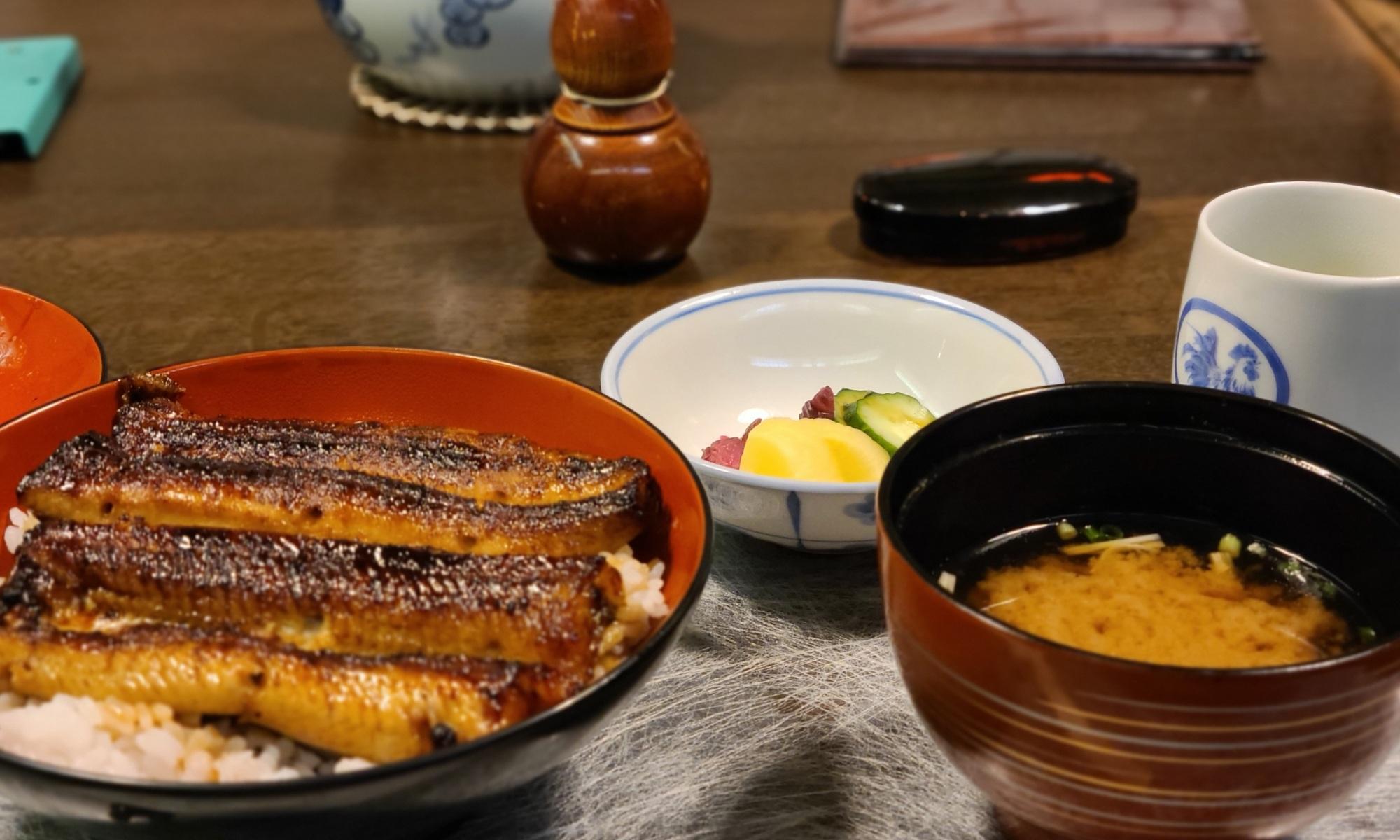 テーブルに鰻丼とみそ汁、漬物が並んでいます。