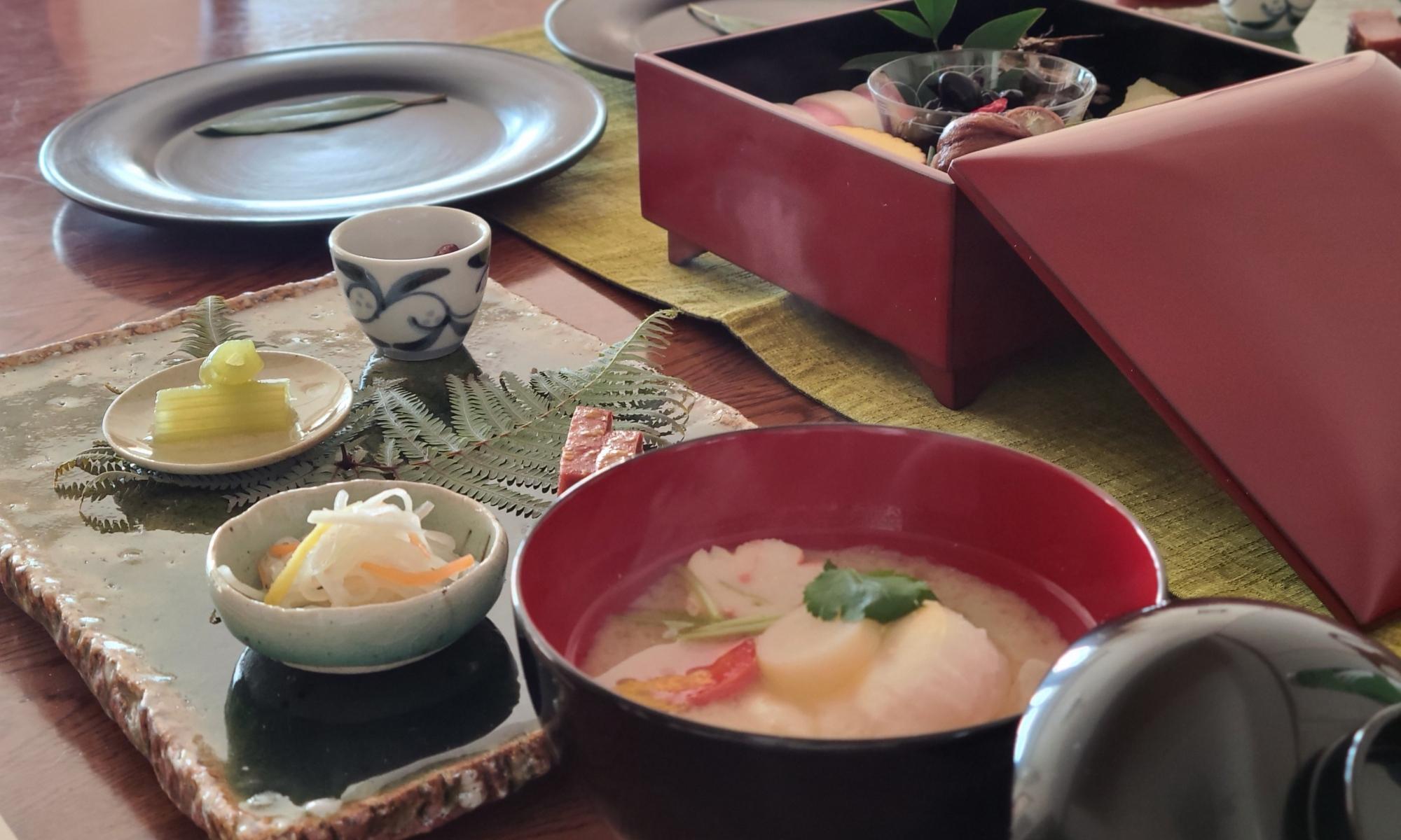テーブルにお重に入ったお節料理や雑煮などが並んでいます。