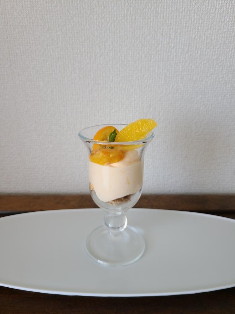 グラスに入ったオレンジのムースの上にオレンジピューレや生の果肉がデコレート