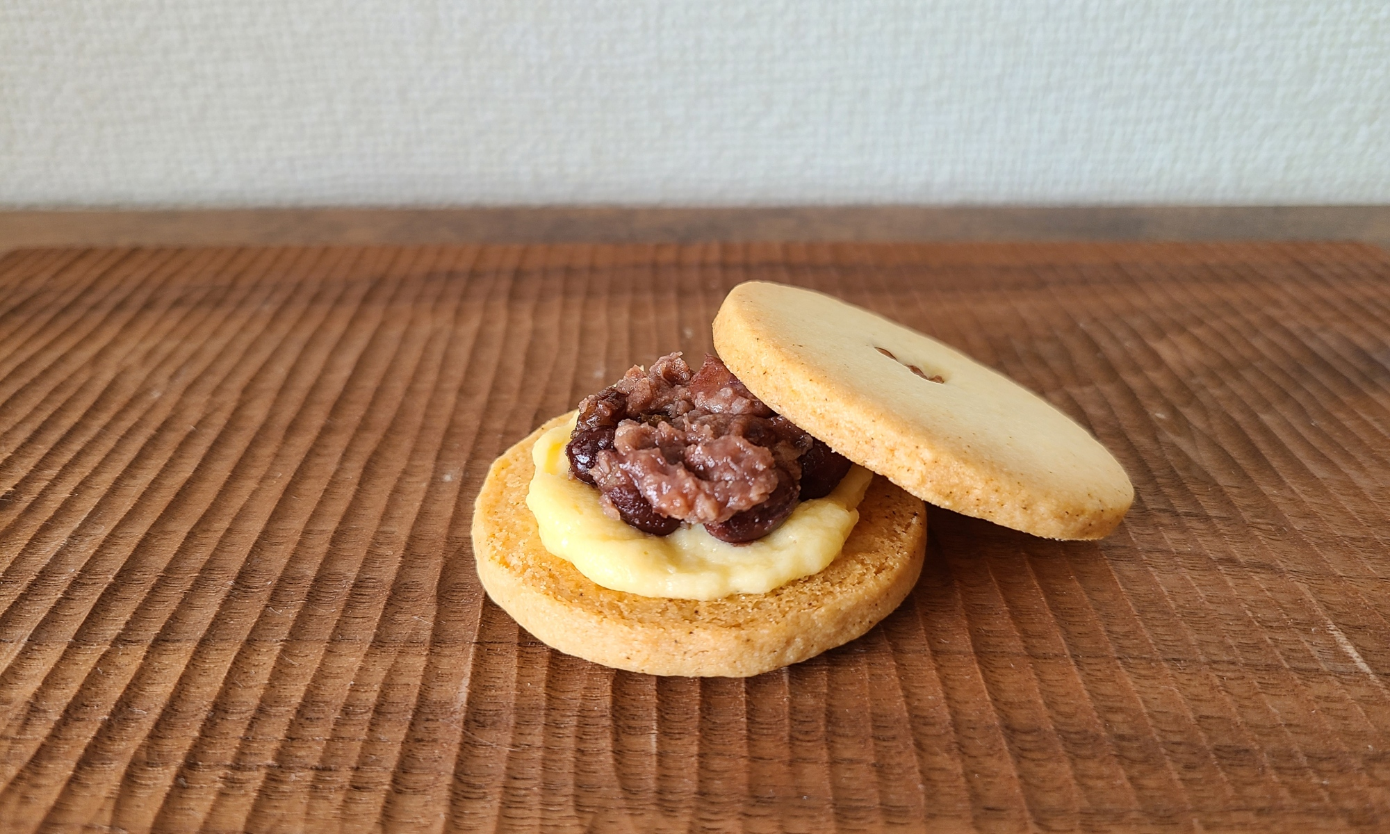 木板の上に発酵小豆とクリームがサンドされたクッキー